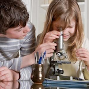 Два подростка смотрят в микроскоп